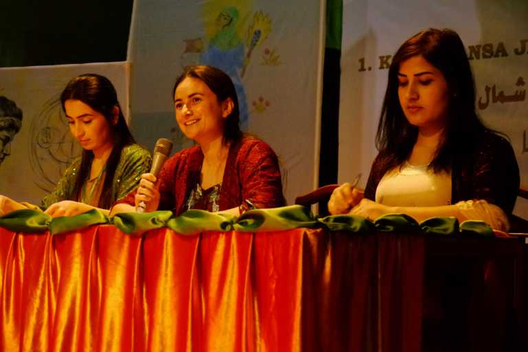 Three women on a panel speaking at  a conference. Kurdish