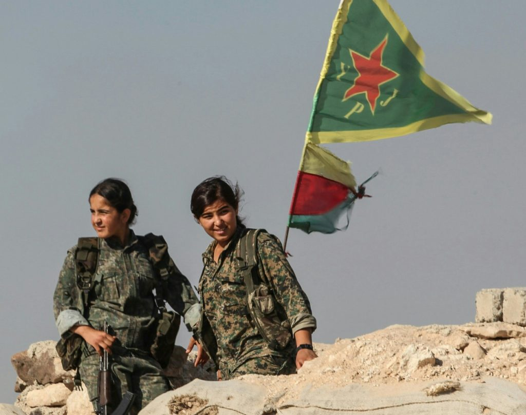 jineology - YPJ fighters with flag in the background.