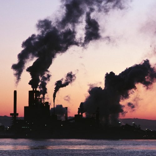 A waterfront factory pumping out clouds of smoke silhouetted against an orange-purple sunset sky, mountains visible in distance